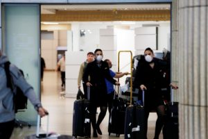 Airline employees wearing masks walk in the arrivals terminal after Israel said it will require anyone arriving from overseas to self-quarantine for 14 days as a precaution against the spread of coronavirus, at Ben Gurion International airport in Lod, near Tel Aviv, Israel March 10, 2020. REUTERS/Ronen Zvulun
